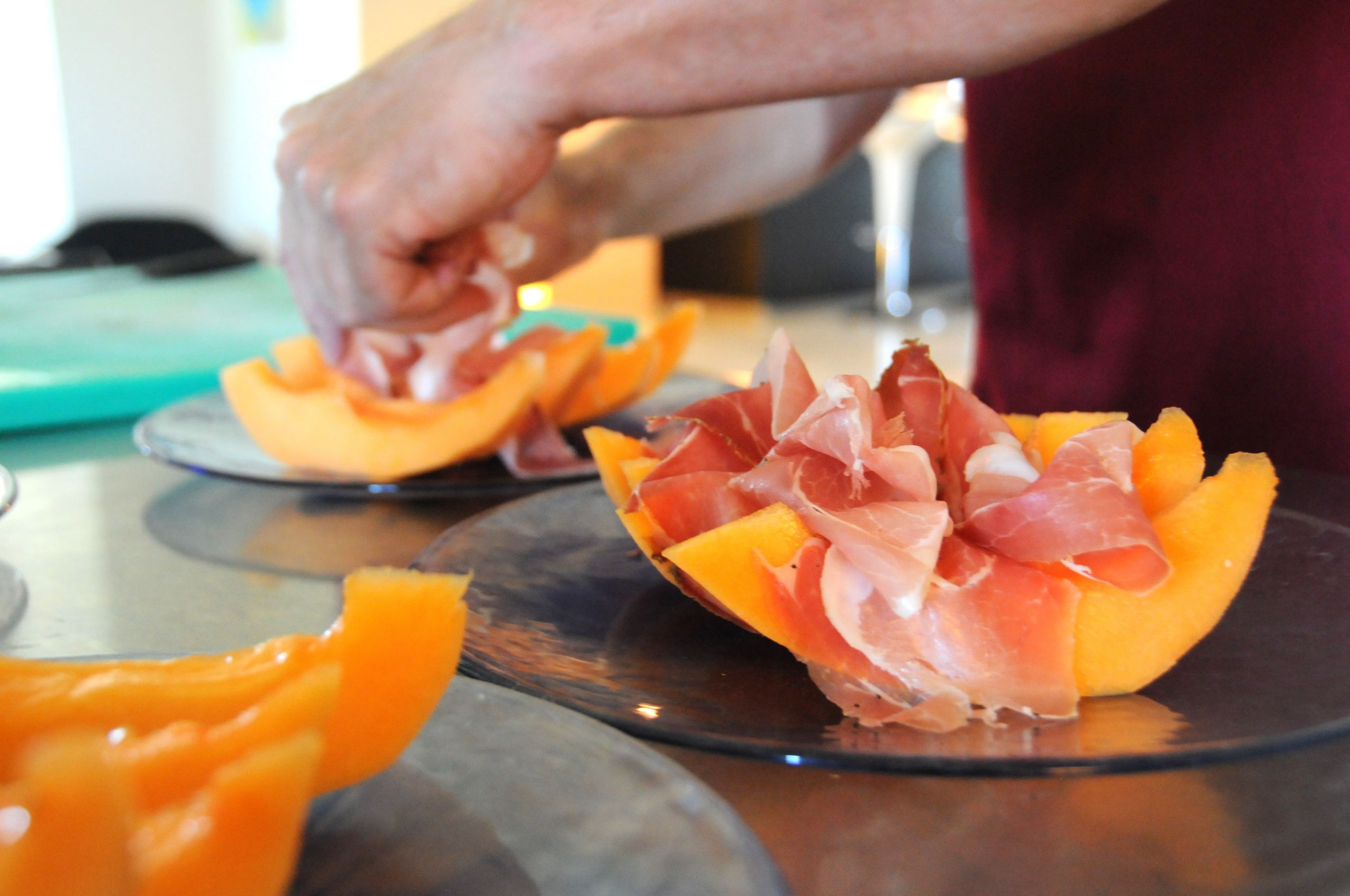 Image showing a hand arranging fine slices of ham atop slices of melon