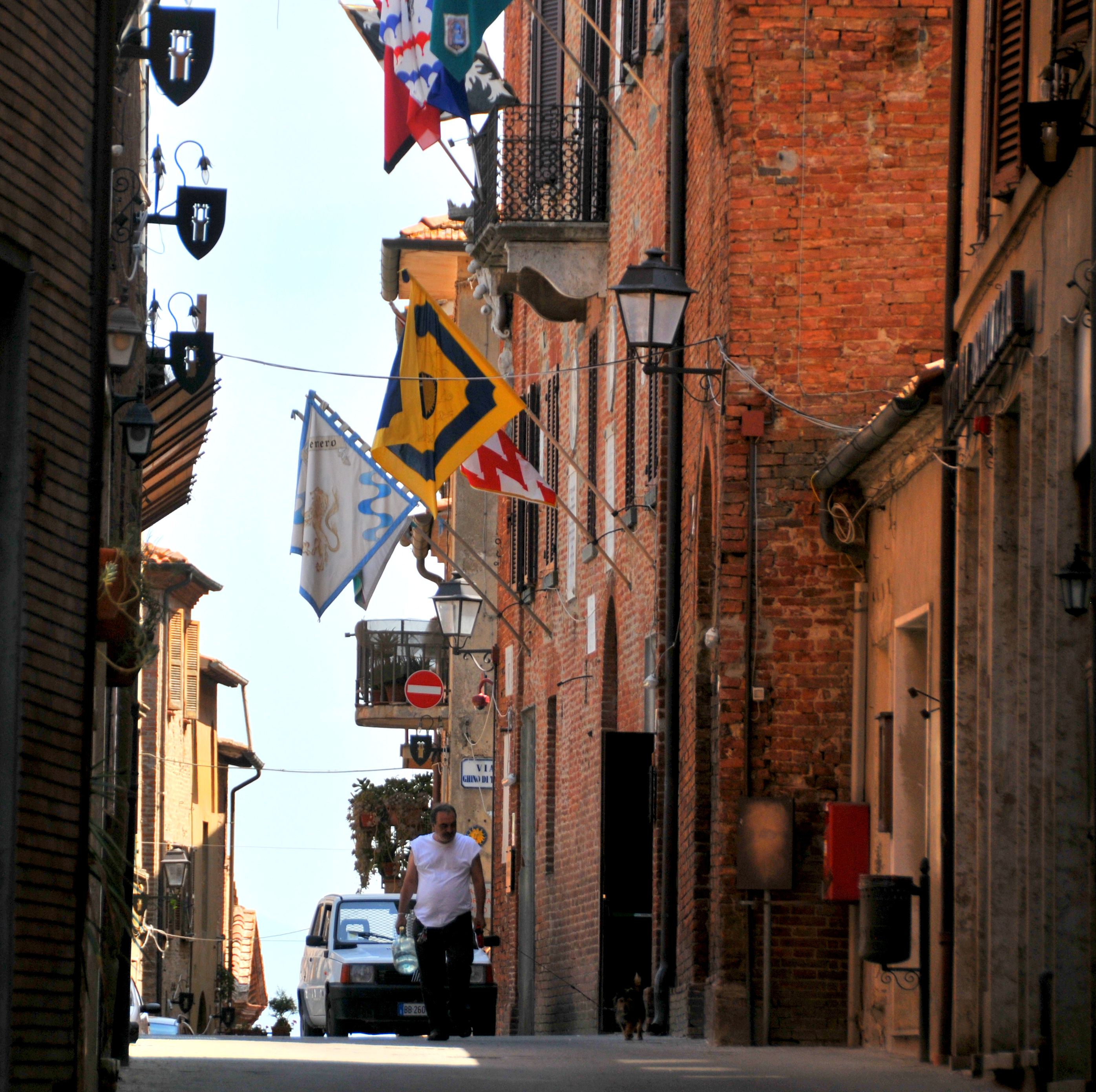 Image showing a red brick Tuscan hill town showing tall narrow buildings and narrow streets with contrada flags flying from the fronts of buildings