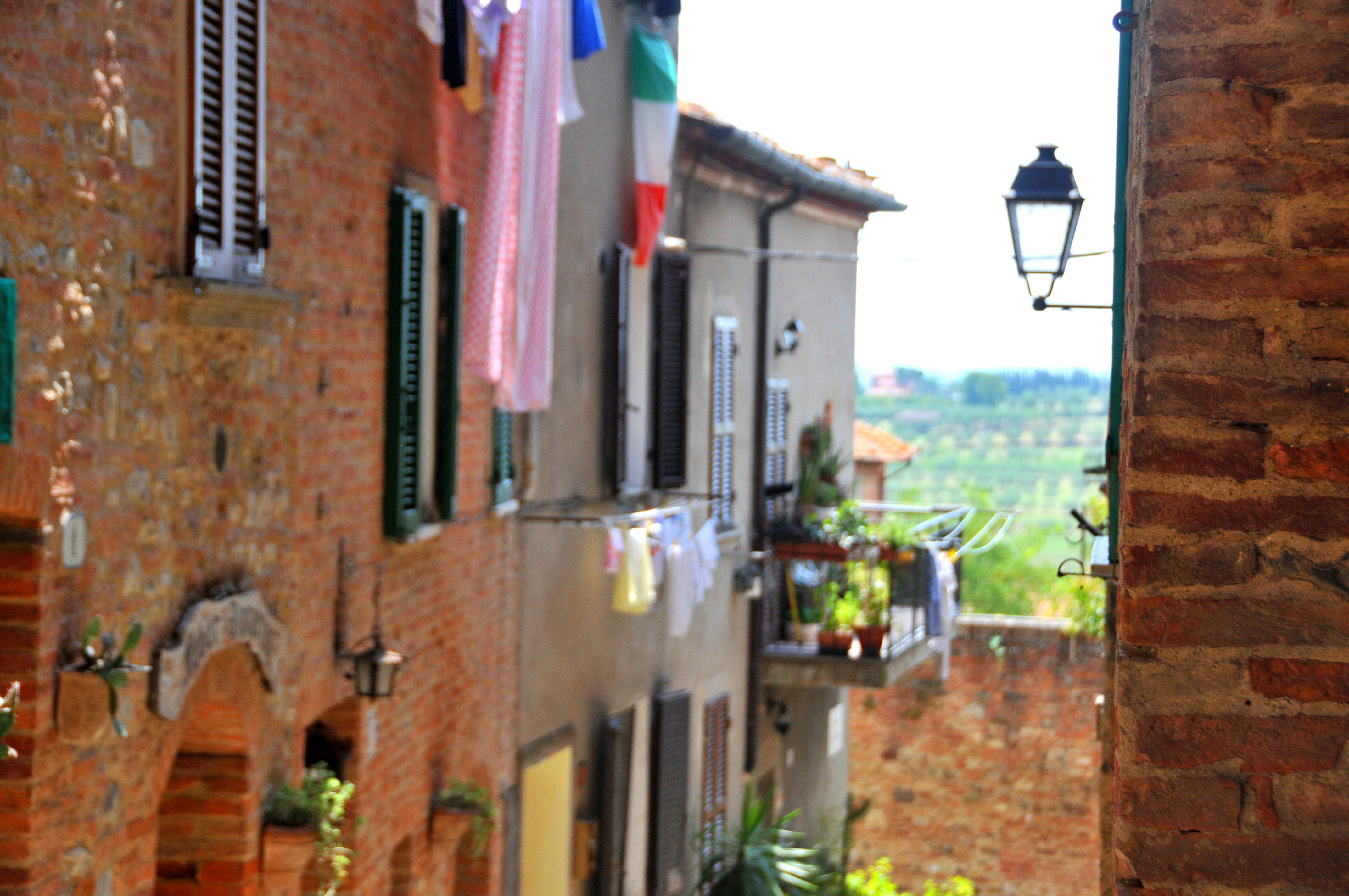 Image of an unspoilt hill town in tuscany showing the town houses in red brick with shuttered windows and the laundry hanging out to dry from balconies in the distance fields and olive groves