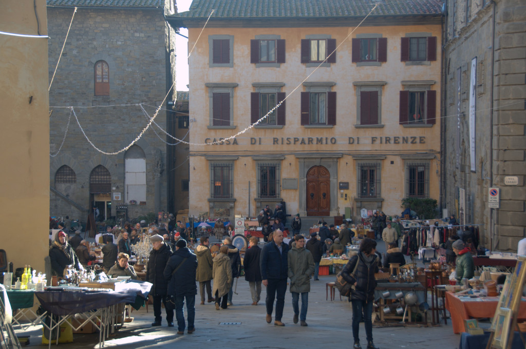 Image showing a tuscan hill town piazza in cortona in winter, a bank facade casa risparmio di firenze in the background people walking and a collectables market in the foreground