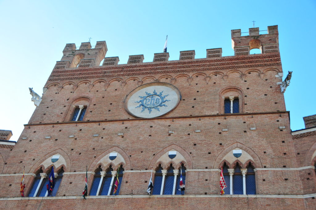 Image showing a medieval building with arched windows and red brick this is the town hall in the Piazza il Campo of Siena