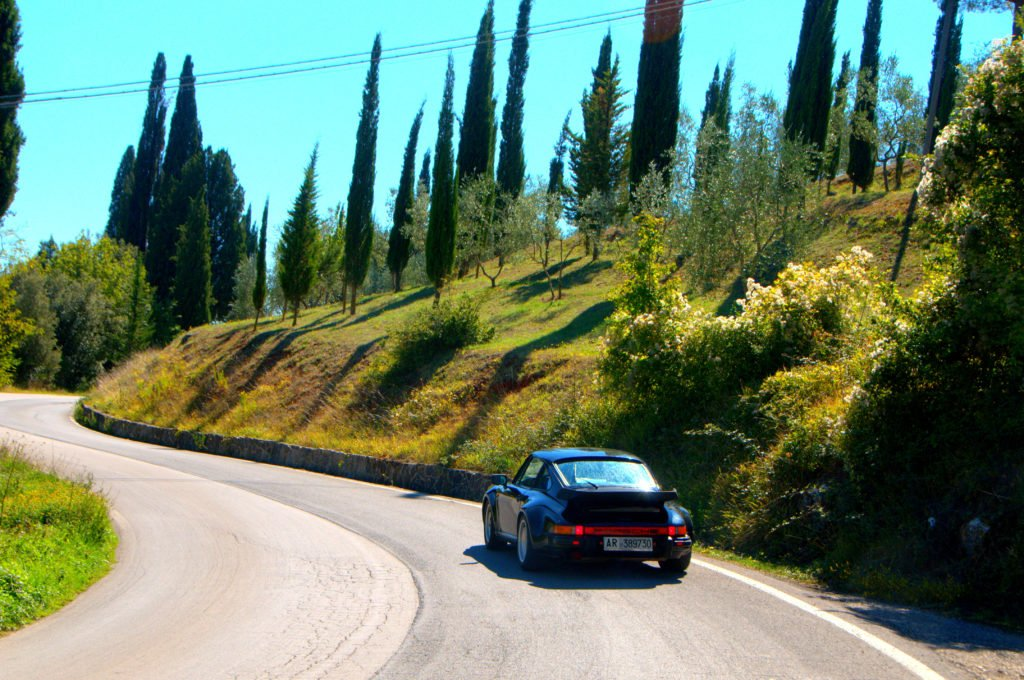 image showing a black porsche 911 turbo on a winding road in Tuscany close to Siena House