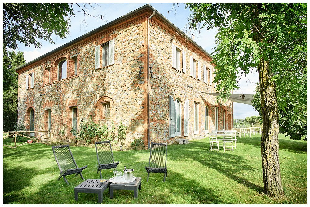Image showing the corner of a leopoldina type tuscan country house built in siena red brick and grey stone. there are white tables under shade on the lawn outside the window doors and at the apex of the corner there are three deck chairs in shade around an ice bucket