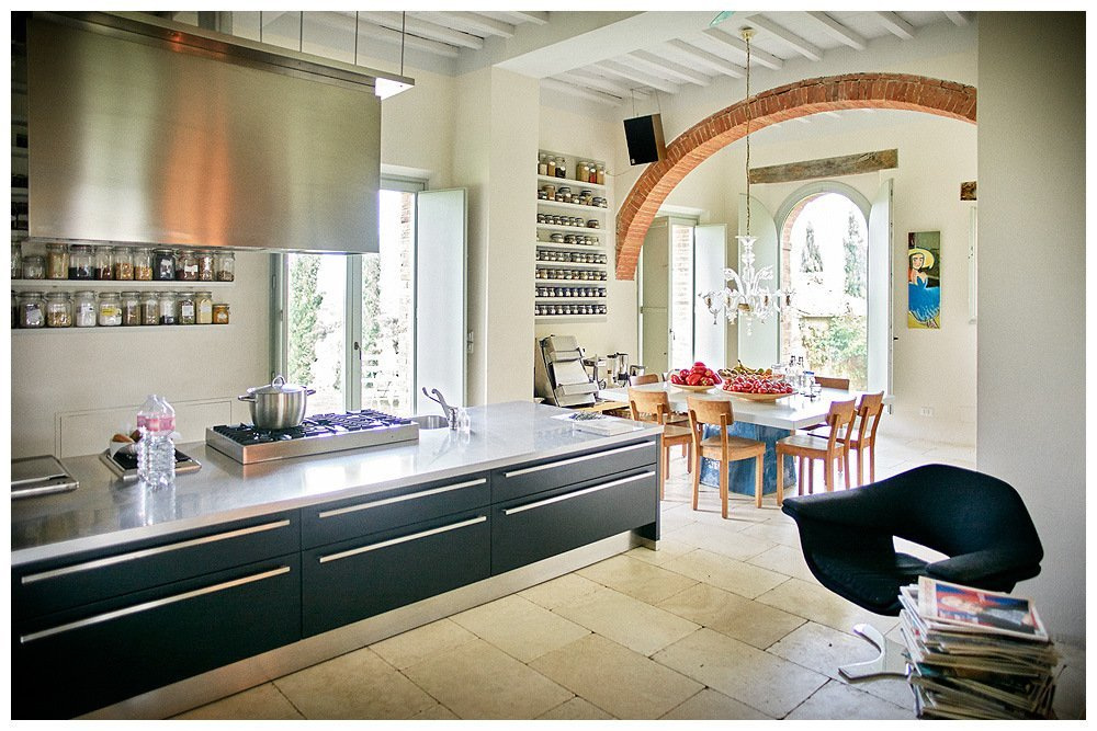 Image showing a tuscan country house restored to boutique hotel with white interior decoration on walls ceiling and floor long low steel topped black kitchen units and large steel extraction hood there are several large window doors and one rich siena red arch over a dining table with sculpted ceramic base and eight chairs there is a black modern italian chair in the bottom right of the image and a murano chandelier over the table
