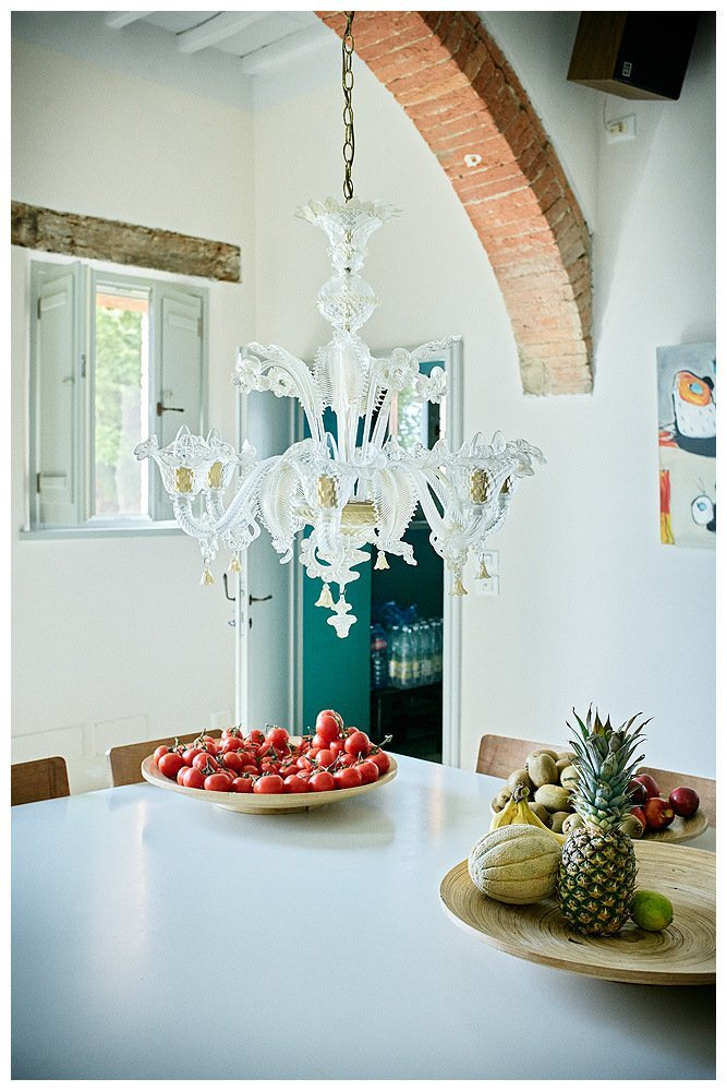 Image showing the white interior of a Tuscan country house with siena red brick arched ceiling and white beams walls and table top modern painting just visible at left abstract airscape by amanda helen atkins