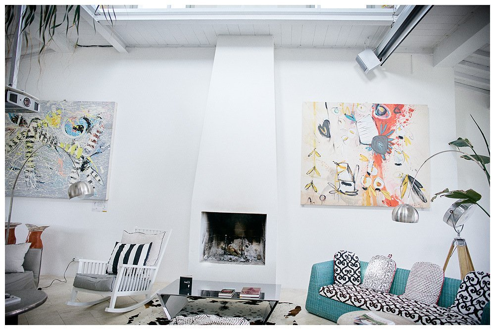 Image showing the restored white interior of a leopoldina style tuscan country house decorated in whites the image shows a central modern fireplace with two large modern painting by artist amanda helen atkins along side furniture by architect paola navone the room is gallery like with light and large walls visible at left a projector and at right a cinema screen above the opening of the tower gallery floor is just visible and at top left the fronds of a tall tree within the room