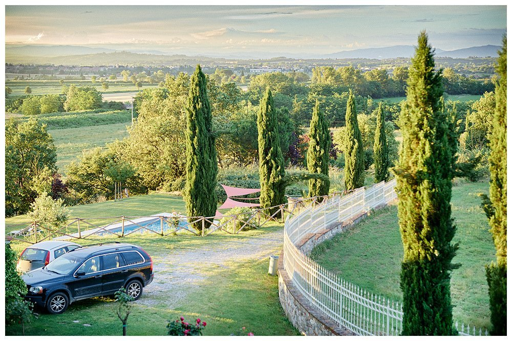 Image showing the scene from the window of a tuscan country house first floor bedroom showing a cypress lined driveway and grey green iron fence a top a brick wall a pool below in lawns two parked cars and views of undulating farm land and villages