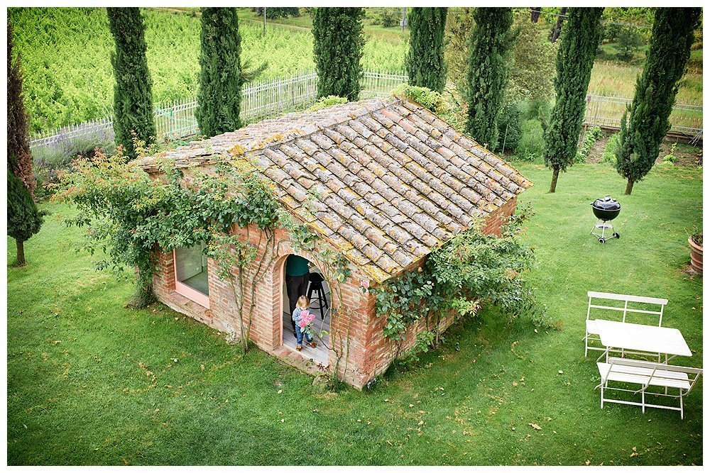 Image showing a tiny stable built in siena red brick with roses climbing the front and hand made tuscan roof tiles. The building sits directly in the grass, in the garden of a country house with cypress trees and vegetable garden beyond. there is a little girl standing in the doorway