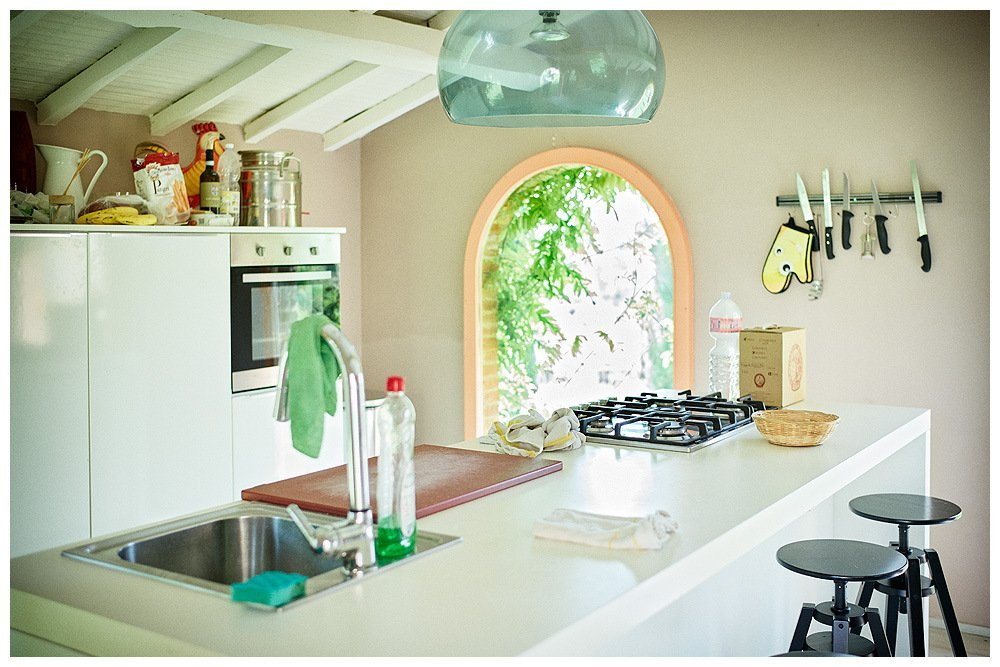 Image showing the restored interior of a tuscan country house outbuilding - a little stable or pigsty - restored to a modern white kitchen. walls are lavender grey and windows are dirty rose pink this is the guest kitchen at a boutique hotel in tuscany