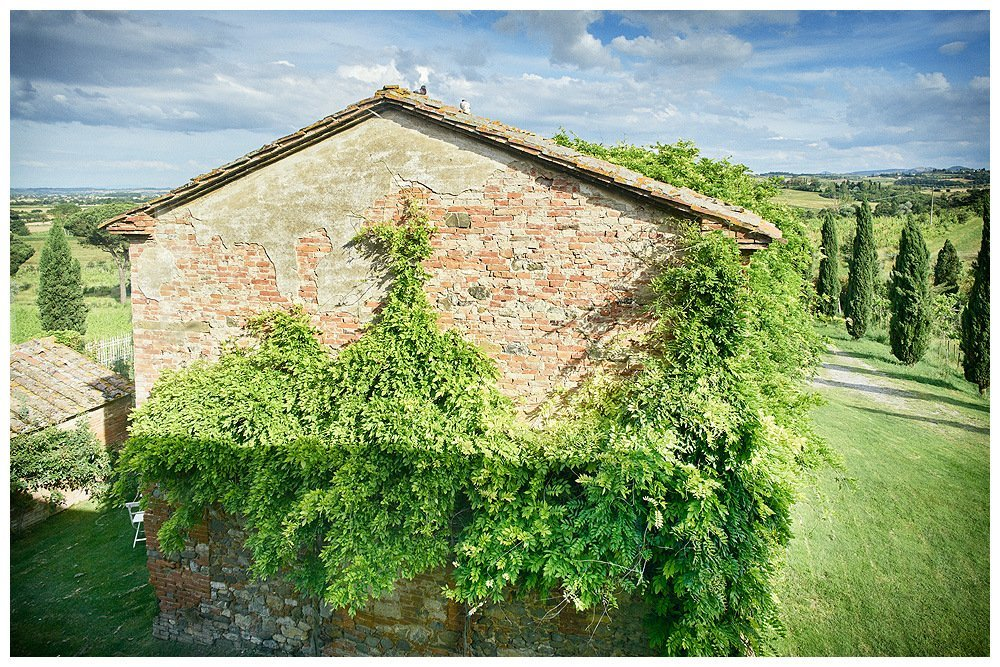 Image showing a tuscan country house in it's original unrestored state. This is a june image and the grass surrounding and plants climbing on the building are brilliant green. There is a second smaller building next to it and both are built in siena red brick. the sky above is blue and the background shows a gently undulating landscape with cypress trees and farms of the val di chiana in siena