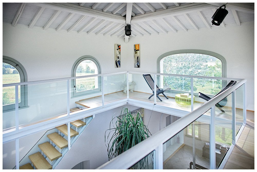 Image by Rene Rickli showing the interior of a leopoldina tuscan country house restored with white interior and open tower with mezzanine or internal gallery circling the interior of the tower the white beamed ceiling with film set light is visible at top and in the middle of the image the glass walls of the mezzanine below at left the descending staircase and the top of a huge palm plant within the room below a project realised by architect and designer