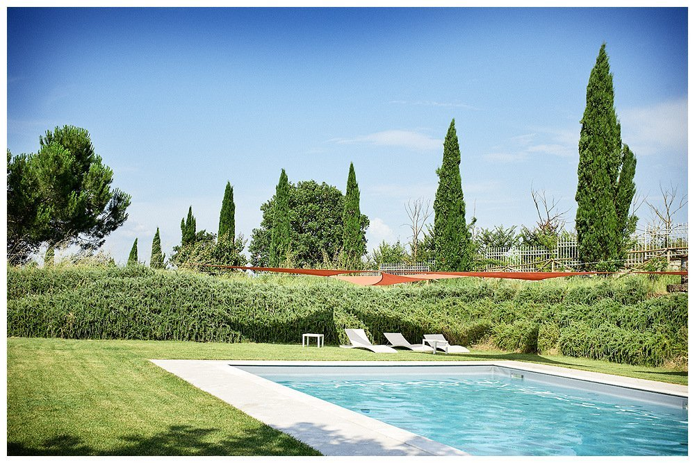 Image showing a pool in bright green lawns at a tuscan country house. three white sun loungers in the background against the rosemary hedges and in the distance a row of cypress trees and fence under blue skies