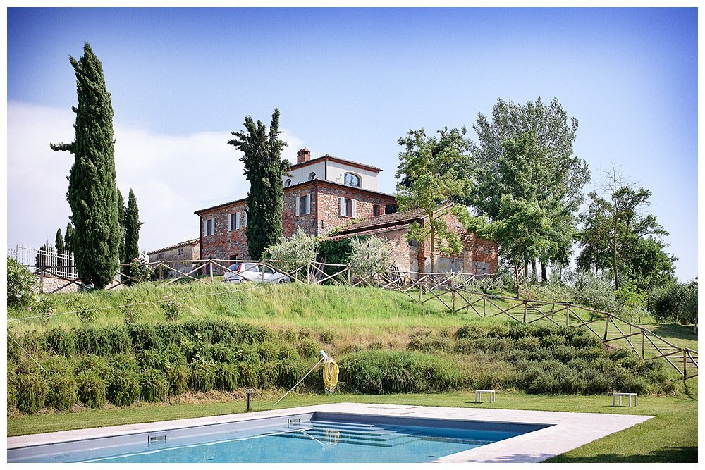Image showing a tuscan country house with white tower third floor and siena red walls below. there is another building separate and between the house and a pool shown in the foreground of the image. A rustic fence, olive acacia and cypress trees are visible in the image