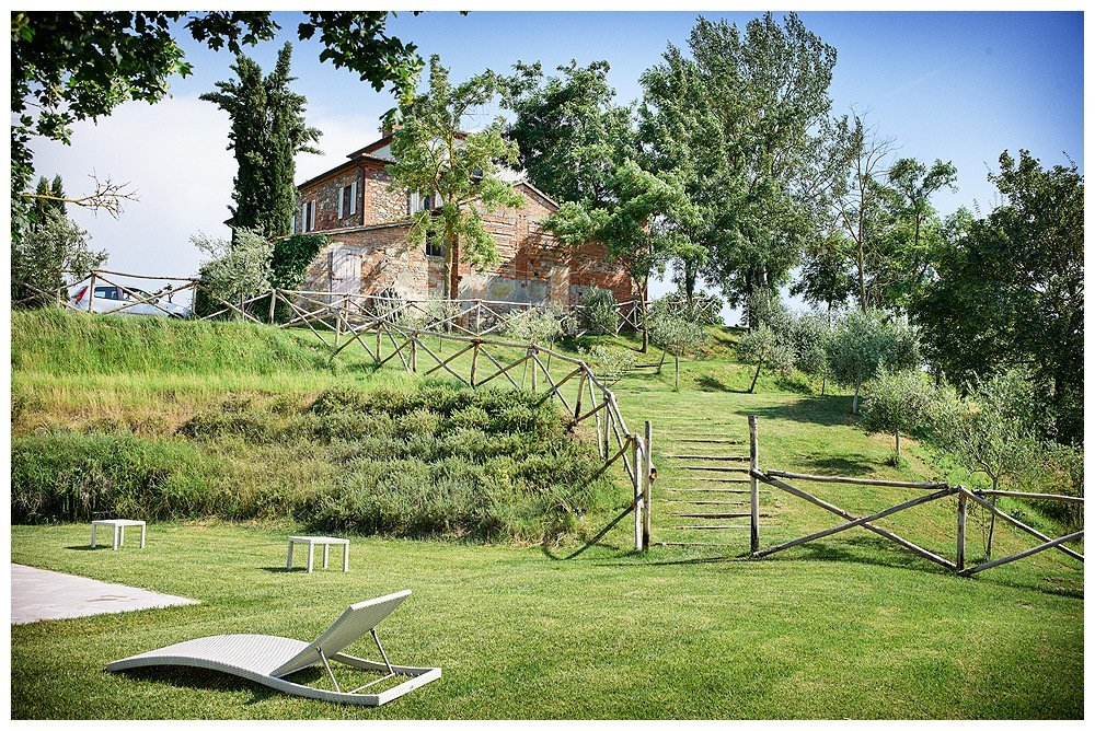 Image showing a lot of lawn and one white lounger in the foreground then steps in the mid ground up to a siena red brick building slightly covered by trees beyond