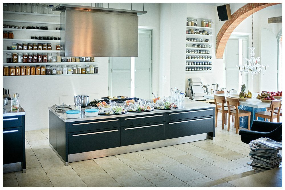 Image showing the white interior of a boutique hotel kitchen the work surfaces in steel large extraction hood in steel one siena red ceiling arch visible over a large table design paola navone in the kitchen too at right of the image a stack of modern painters magazines and behind the kitchen a store of home made jams and marmalades presented as a work of art image by rene rickli