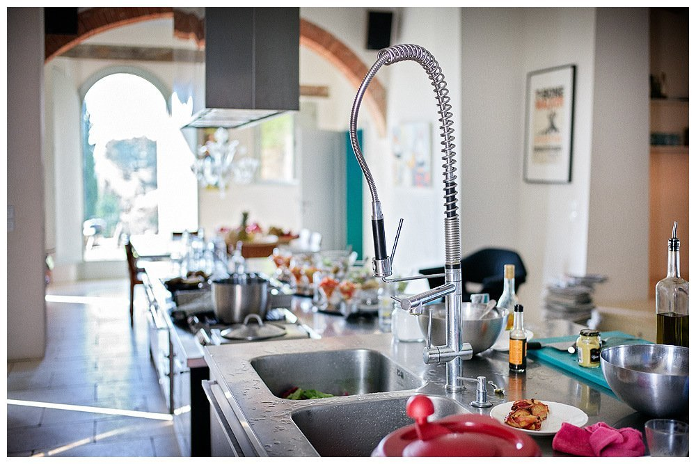Image showing the white interior of a restored tuscan country house the room shown is an open hotel kitchen with dining table within there are several breakfasts prepared lined up out of focus and in the foreground the wash up area photo of siena house by rene rickli