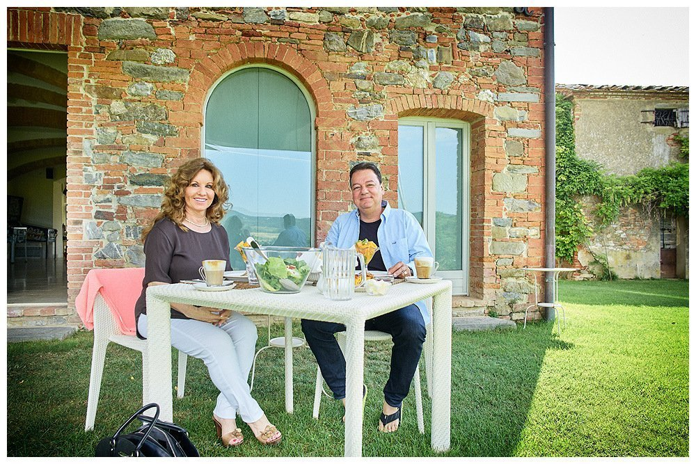 Image showing two people seated at a white table outside a tuscan country house eating breakfast. This is the photographer rene rickli during his stay at siena house. The table is on lawn outside a siena red brick building