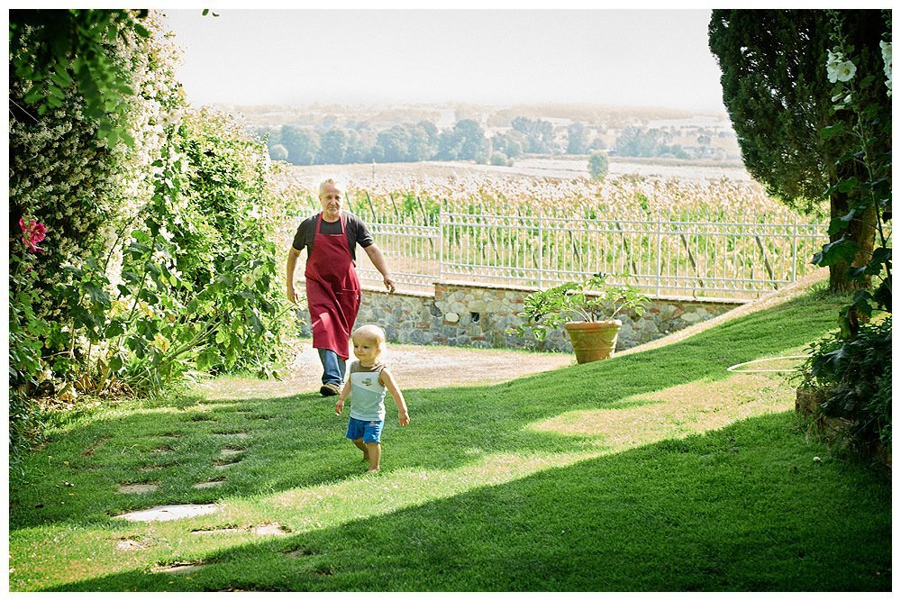 Image showing a man in a red apron and a toddler dressed in blue in a tuscan country garden within a fenced villa in the province of siena