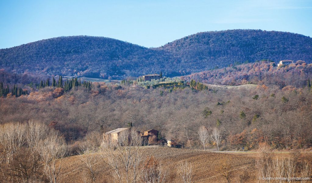 Image showing tuscany winter landscape a hilly ridge trequanda countryside farm house in mid and foreground siena red ochre and umber colours with deep hazy blue distant trees in cypress green azure blue sky and bare winter trees view from boutique hotel garden