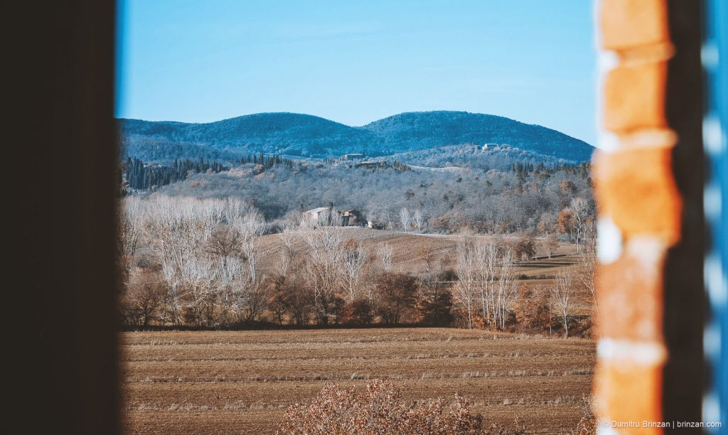 Image showing winter tuscany views distant rolling hills coloured cobalt blue bare trees and country houses in the mid ground white topped bare poplars along the edge of a sienna brown field siena brown & ochre soil scene is viewed from within a property window edge visible at foreground left and right view from boutique hotel
