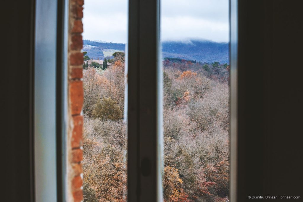 Image showing red siena brick window frame with multi coloured trees viewed from the window under a misty sky and cypress trees beyond
